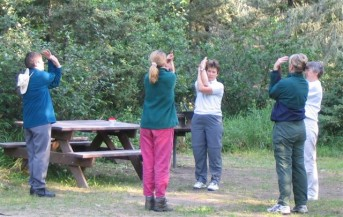 All women's group doing pre-paddling stretches before launching the canoe trip